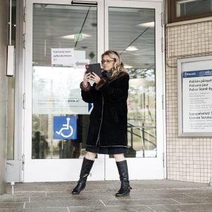 Päivi Räsänen kuvaa itseään Pasilan poliisitalon edustalla.