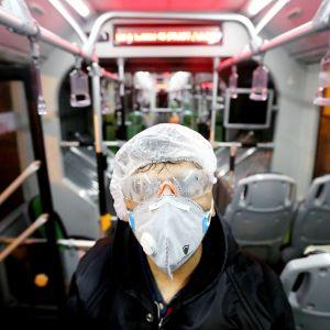 Kasvonsa suojannut työntekijä siivoaa linja-autoa Teheranissa.
