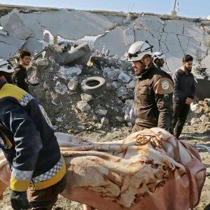 Valkoiset kypärät -järjestön jäsenet siirtävät ruumista Syyrian Maaret Misrinissä.
