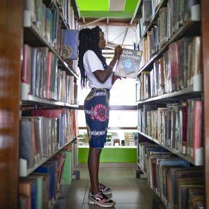 Naisopiskelija yliopiston kirjastossa.