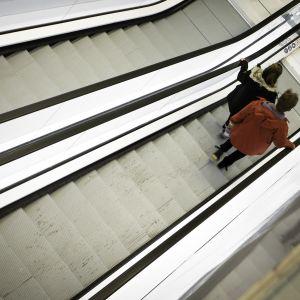 Nainen ja mies kauppakeskuksen rullaportaissa.