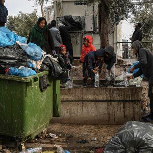 Pakolaiset täyttävät vesipulloja jäteastioiden keskellä Morian pakolaisleirillä.