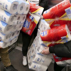Ihmisiä runsaine vessapaperi - ja talouspaperiostoksineen hississä Ruoholahden kauppakeskuksessa Helsingissä.