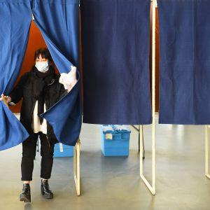 Hengityssuojainta käyttävä nainen tulee ulos äänestykopista.