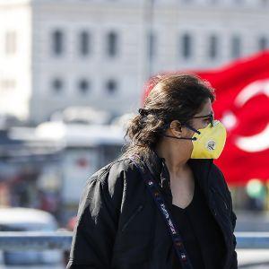 Hengityssuojainta käyttävä nainen kadulla