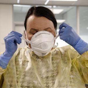 Nainen asettaa hengitysmaskia kasvoilleen.