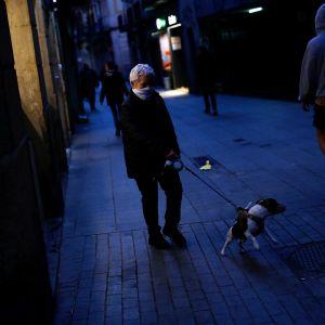Kaksi koiranulkoiluttajaa ohittavat toisensa kadulla Barcelonassa.