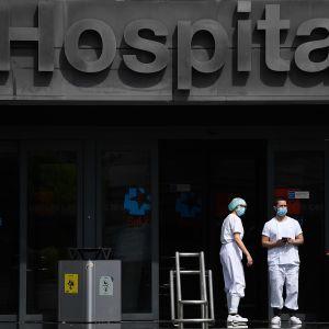 Kaksi hoitohenkilöstöön kuuluvaa seisoo sairaalan edustalla Madridissa.
