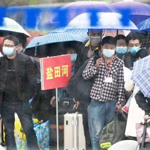 Hengityssuojaimiin pukeutuneita matkustajia Manchengin rautatieasemalla Kiinan Hubeissa.