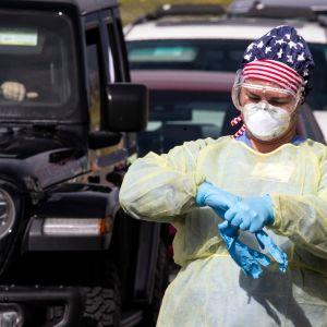 Hoitaja vaihtaa hanskoja otettuaan autoilijalta näytteen