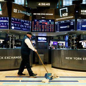 Mies lakaisee lattiaa New Yorkin pörssissä.