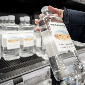 Asikas ottaa alkoholijuomapulloa Alkon hyllystä.
