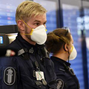 Poliiseja Helsinki-Vantaa lentokentällä hengityssuojaimet kasvoillaan 27. maaliskuuta.