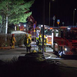 Paloautoja ja palomiehiä kadulla.