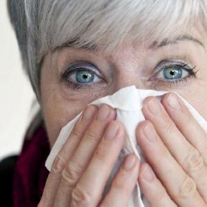 Harmaatukkainen nainen, jolla on kuumeiset silmät, painaa nenäliinaa kasvoilleen.