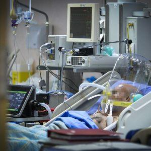 Potilas makaa sairaalavuoteessa hengitysmkoneessa, sängyn ympärillä useita sairaalalaitteita. Kasvot pixelöity.