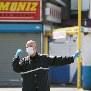 Poliisi ohjaa liikennettä New Yorkissa maski kasvoillaan.