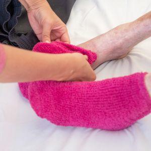 Hoitaja laittaa sukkaa vanhuksen jalkaan.