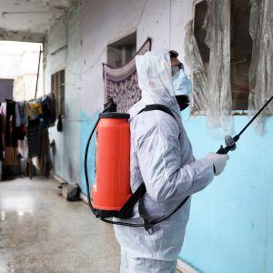 Violet Organization -järjestön vapaaehtoistyöntekijä desinfioi pakolaisten asuntoja Idlibissa Syyriassa.