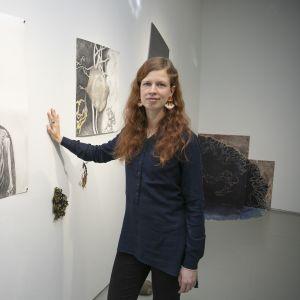 Nainen seisoo taidenäyttelyssä teoksen edessä.