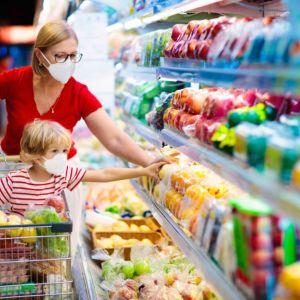 Nainen ja lapsi ruokakaupassa. Lapsi istuu ostoskärryissä. Molemmilla on hengityssuojain.