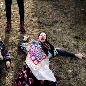 Ketuksi ja pääsiäisnoidaksi pukeutuneet lapset makaavat maassa ja huutavat.