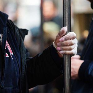 Matkustaja metrossa suojakäsineet kädessä.