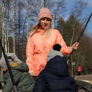 Henna Helne kahden poikansa kanssa puistossa.