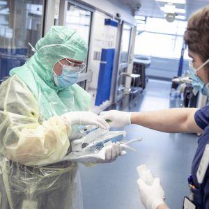 Suojapukuun pukeutunut hoitaja ja avustava hoitaja koronapotilaiden testaamiseen ja hoitoon tarkoitetulla osastolla Turun yliopistollisessa keskussairaalassa Tyksissä.