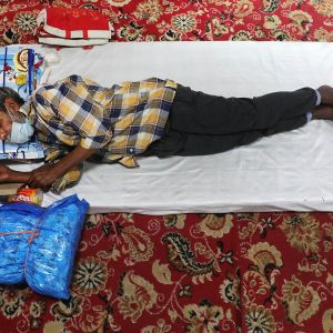 Kuvassa mies makaa patjalla leposuojassa Intian Delhissä.