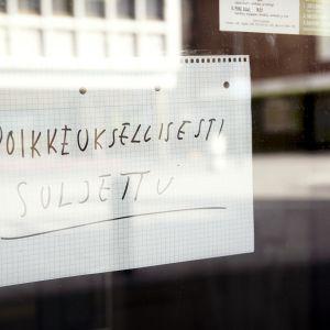 Poikkeuksellisesti suljettu -lappu ravintolan ikkunassa.