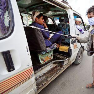 Vapaaehtoistyöntekijä desinfioi julkisessa liikenteessä käytettävää tila-autoa Jemenin Sanaassa.
