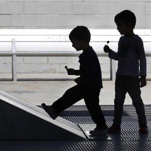 Kahden lapsen siluetit kadulla. Lapsilla on käsissään tikkarit.