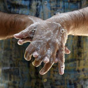 Miehen kädet saippuavaahdossa.