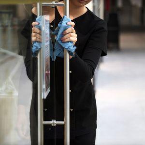 Työntekijä desinfioi myymälän ovenripaa kauppakeskuksessa.