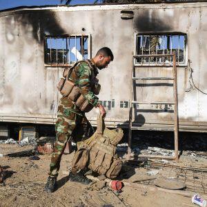 Irakilaissotilas tutkimassa Isisin tekemää hyökkäystä.