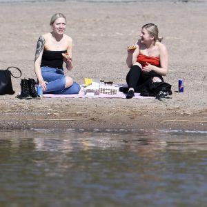 Ihmiset nauttivat lämpimästä päivästä Ispoisten uimarannalla Turussa tiistaina.
