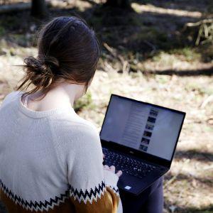 Kuvassa nainen tekee etätöitä tietokoneella metsässä.