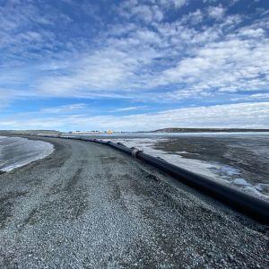 Boliden Kevistan kaivos Sodankylässä. Näkymä suuren rikastushiekkajätealtaan padon päältä.  Allas oikealla on ajettu vähälle vedelle. Horisontissa keltainen kartio on kaivoksen rakennus, josta vasemmalle neljä kilomertiä pitkä jätekiviläjä. Altaan takana nousee Kevitsavaara joka on kohta matalampi kuin kaivoksen jätekivialue.