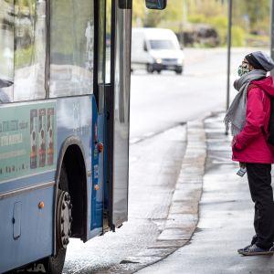 Matkustaja odottaa yksin pääsyä bussin sisään koronavirusmaski kasvoillaan.