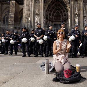 Hymyilevä, käsiään taputtava nainen polvillaan Kölnin tuomiokirkon edessä. Maassa reppu, termospullo ja eväspussi. Takana rivi poliiseja.