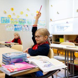 Tallinnan Reaalikoulussa pidetään huolta turvaväleistä. Ensimmäistä luokkaa käyvä Mia Helena viittaa äidinkielen tunnilla.