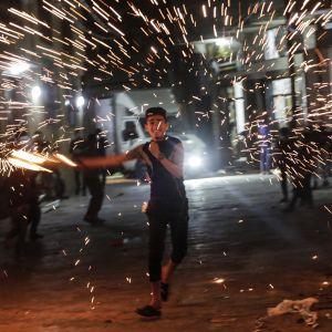 Palestiinalaispoika heiluttaa kotitekoista ilotulitetta Jabaliassa Gazan kaistalla.