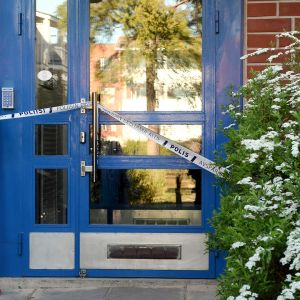 Poliisin sulkunauhaa kerrostalon alaovessa Espoon Mäkkylässä tiistaina 26. toukokuuta.