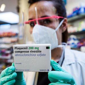 Farmaseutti näyttää hydroksiklorokiini pakettia.