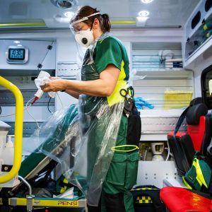 Kuvassa on ruotsalainen hoitaja, joka desinfioi ambulanssia.
