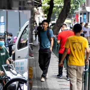 Ihmisiä kävelemässä Guangzhoun kaduilla 20. huhtikuuta.