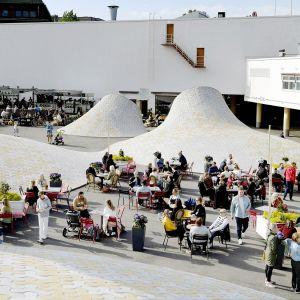 Ihmisiä Lasipalatsin Laiturin terassilla Helsingissä.