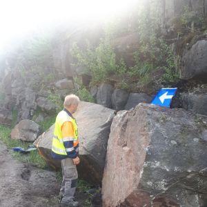 Mies katselee kallioileikkauksesta irronneita isoja kivenmurikoita.