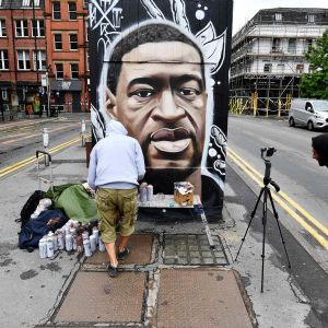 Kuvassa maalataan muraalia, joka esittää poliisin surmaamaa värillistä aseetonta miestä, George Floydia.